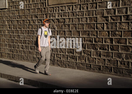 Boy walking along the street, wearing headphones and holding cigarette, in Carrer del Carme, El Raval, Barcelona. - Stockfoto