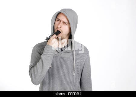 A man trying to commit suicide with a gun pointed at his mouth - Stock Photo