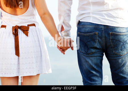 Happy couple in love holding hands walking away near the sea - Stockfoto