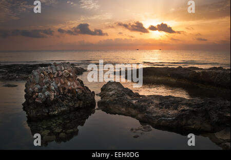 Sunset over the Sea and Rocky Coast with Ancient Ruins in Mahdia, Tunisia - Stock Photo
