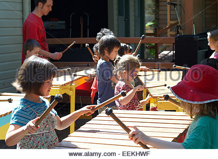 primary school kids children playing marimbas in a performance - Stock Photo
