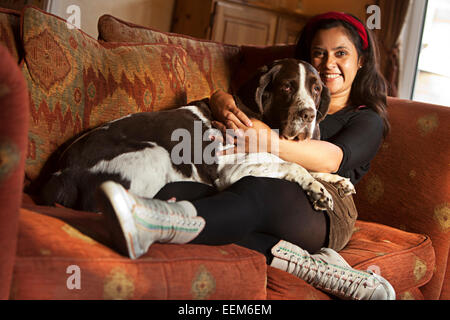 Woman sitting on couch with her dog - Stock Photo