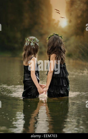 Two girls (8-9, 10-11) holding hands and watching sunset - Stock Photo