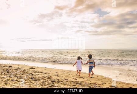 Jungen und Mädchen (2-3) Hand in Hand zu Fuß am Strand - Stockfoto