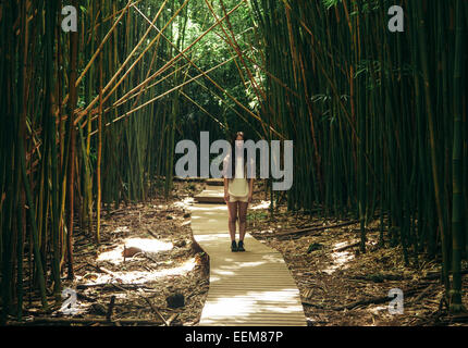USA, Hawaii, Girl (12-13) standing on wooden boardwalk in bamboo forest - Stockfoto