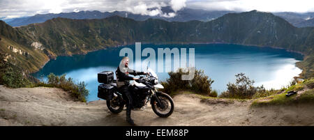 Ecuador, Man on motorbike posing against lake at Laguna Quilotoa - Stock Photo