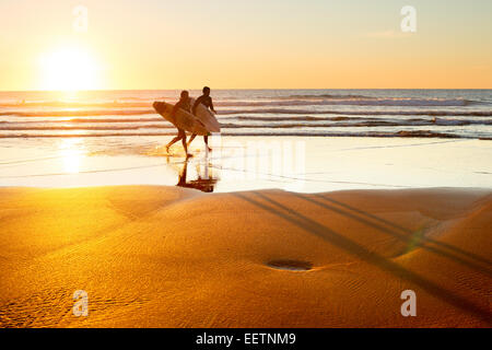 Two surfer running on the beach at sunset. Portugal has one of the best surfing scenes in Europ - Stock Photo