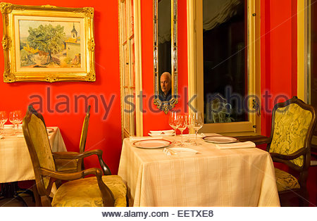 Reflection of a mature male in an empty dining room - Stock Photo