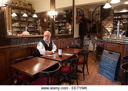 Mature male waiting to dine in a French bistro - Stock Photo