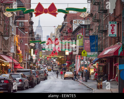 Little Italy all dressed for Christmas. Red bows. lights & a Merry Christmas sign liven up New York's little italy - Stock Photo