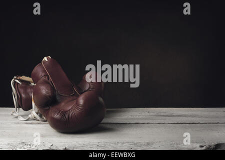 Boxing Gloves lying on two wooden Planks - Stock Photo