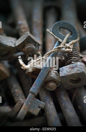 old key hidden in rusty bolts - Stock Photo