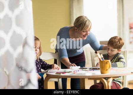 Mother playing with daughter and son (4-5, 6-7) - Stock Photo