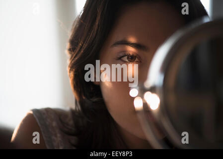 Young woman looking into mirror - Stock Photo