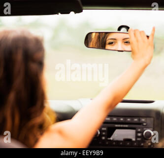 Reflection of young woman in rear view mirror - Stock Photo
