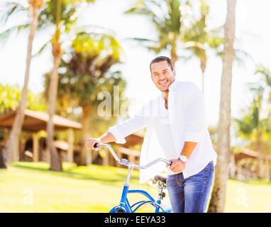 USA, Florida, Jupiter, Man with bicycle with palm trees in background - Stock Photo