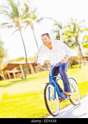 USA, Florida, Jupiter, Man riding bike - Stock Photo