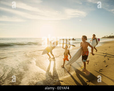 USA, California, Laguna Beach, Family with three children (6-7, 10-11, 14-15) with surfboards on beach - Stock Photo