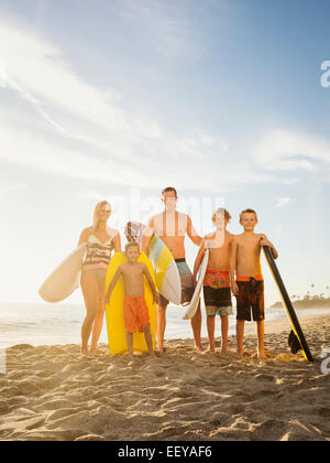 USA, California, Laguna Beach, Portrait of family with three children (6-7, 10-11, 14-15) with surfboards on beach - Stock Photo