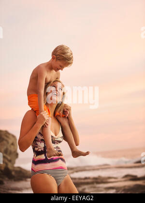USA, California, Laguna Beach, Mother carrying son (6-7) on shoulders outdoors - Stock Photo