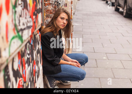 Hipster girl sitting on the street. - Stock Photo
