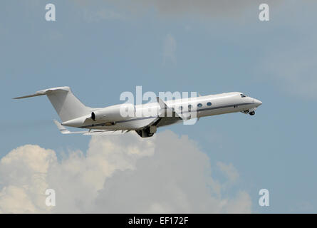 Business charter jet taking off and retracting gear - Stock Photo
