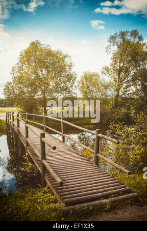wooden foot bridge over a small river - Stock Photo