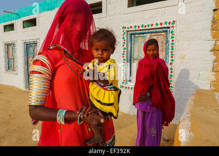 Unidentified woman her child and sister are standing in front of their traditionally painted house in a village - Stock Photo