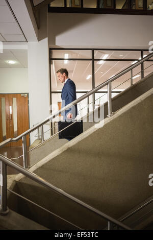 Businessman going down the stairs - Stock Photo