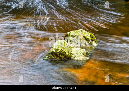 MOSS COVERED ROCKS IN A SCOTTISH HIGHLAND STREAM WITH WATER TINTED BY PEAT - Stockfoto