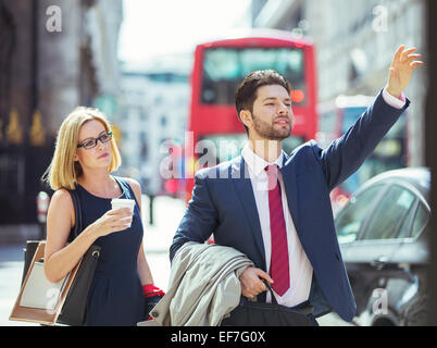 Business people hailing taxi in city - Stock Photo