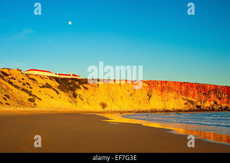 Surfboard on the ocean beach at sunset. Full moon in the sky. Sagres, Portugal - Stock Photo
