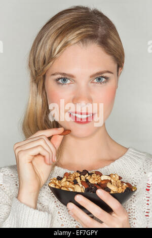 Portrait of a beautiful woman eating dried fruit - Stock Photo