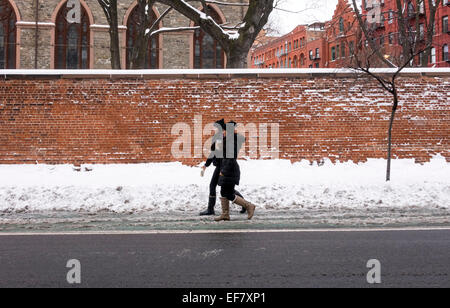 Two young Asian women walking on snow-covered street in winter in New York City - Stockfoto