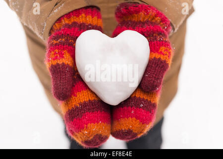 Woman in red mittens holding a heart made of snow, closeup of hands, romantic concept - Stock Photo