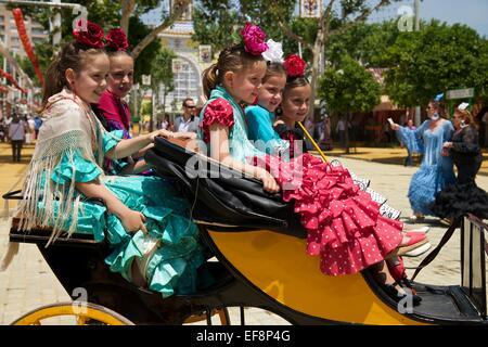 Girls, flamenco dancers at the Feria de Abril, Seville, Andalucía, Spain - Stock Photo