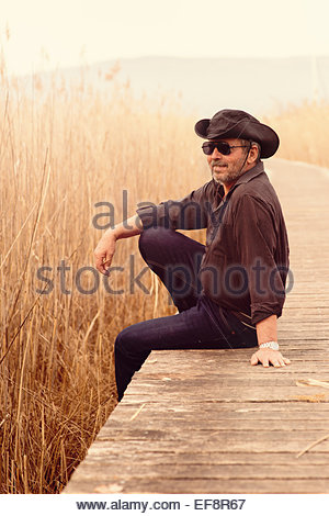 Portrait of senior man wearing sunglasses and cowboy hat sitting on edge of wooden footbridge - Stock Photo