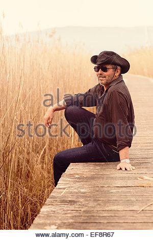 Portrait of senior man wearing sunglasses and cowboy hat sitting on edge of wooden footbridge - Stock Photo