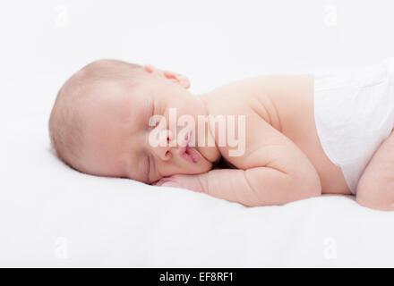 Newborn baby boy sleeping on stomach - Stock Photo