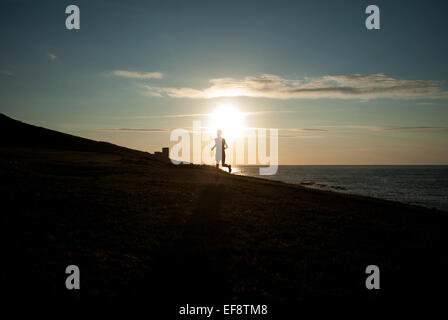 Silhouette of man running on beach at sunset, Galicia, Spain - Stock Photo