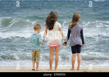 Bulgaria, Two girls (8-9) and boy (4-5) standing at by surf line holding hands looking at sea - Stock Photo