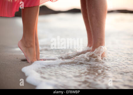 Couple standing in water on beach - Stock Photo