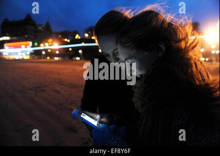 Two teenage English girls texting and face booking on the beach in Scarborough, - Stock Photo