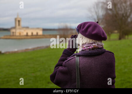 Elderly woman wearing a mauve beret and coat and looking through binoculars at Normanton Church on Rutland Water. - Stock Photo