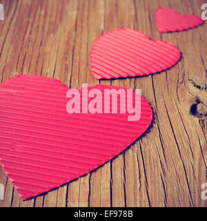 some red hearts of different sizes on a rustic wooden surface, with a filter effect - Stock Photo
