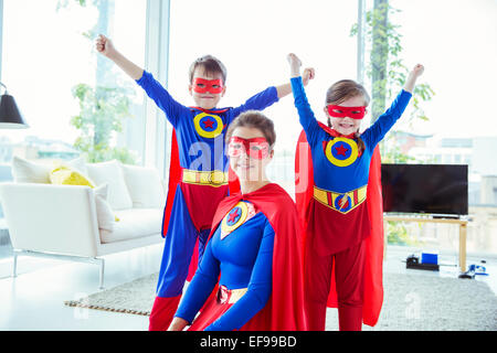 Superhero children and mother smiling in living room - Stock Photo