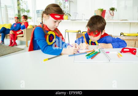 Superhero children drawing at table - Stock Photo