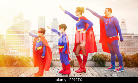 Superhero family standing with arms outstretched on city rooftop - Stock Photo
