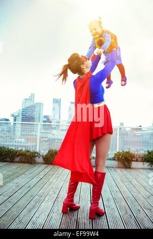 Superhero mother playing with daughter on city rooftop - Stock Photo