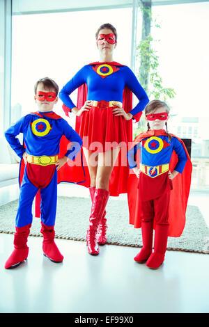 Superhero mother and children standing in living room - Stock Photo